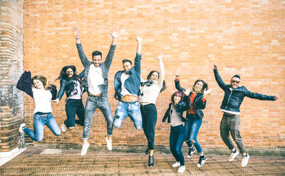 Happy friends millennials jumping and cheering against brick wall in the city - Friendship lifestyle and team concept with young people millenial having fun together - Teal and orange vintage filter
